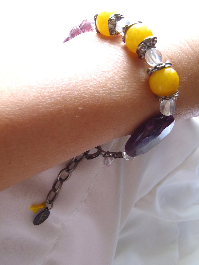 braclet with combination of yellow round jade and purple glass bead shown on a lady's wrist