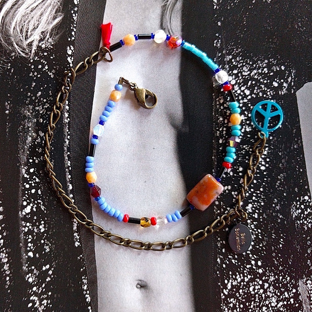 handmade friendship bracelets with colors of blue red amber and clear beads on alternate background
