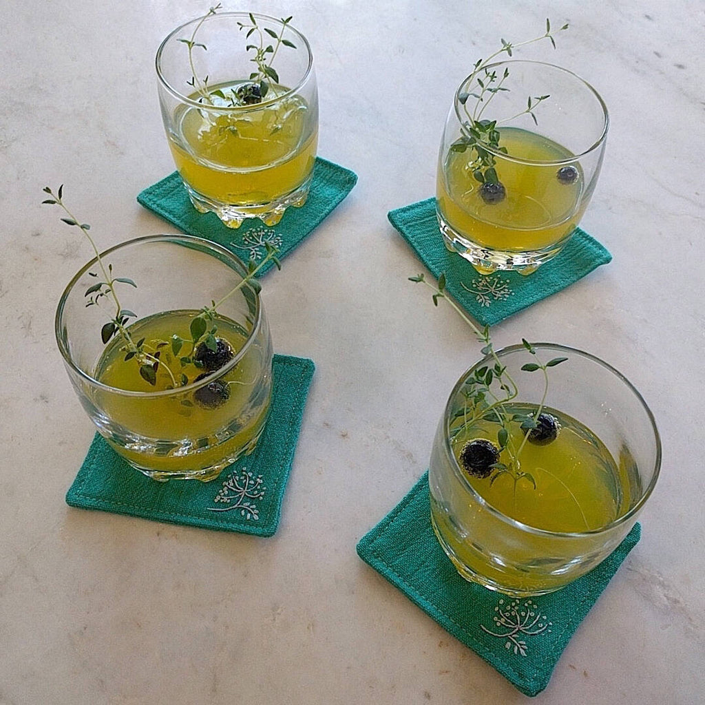 set of four teal green coasters shown with drinks on top