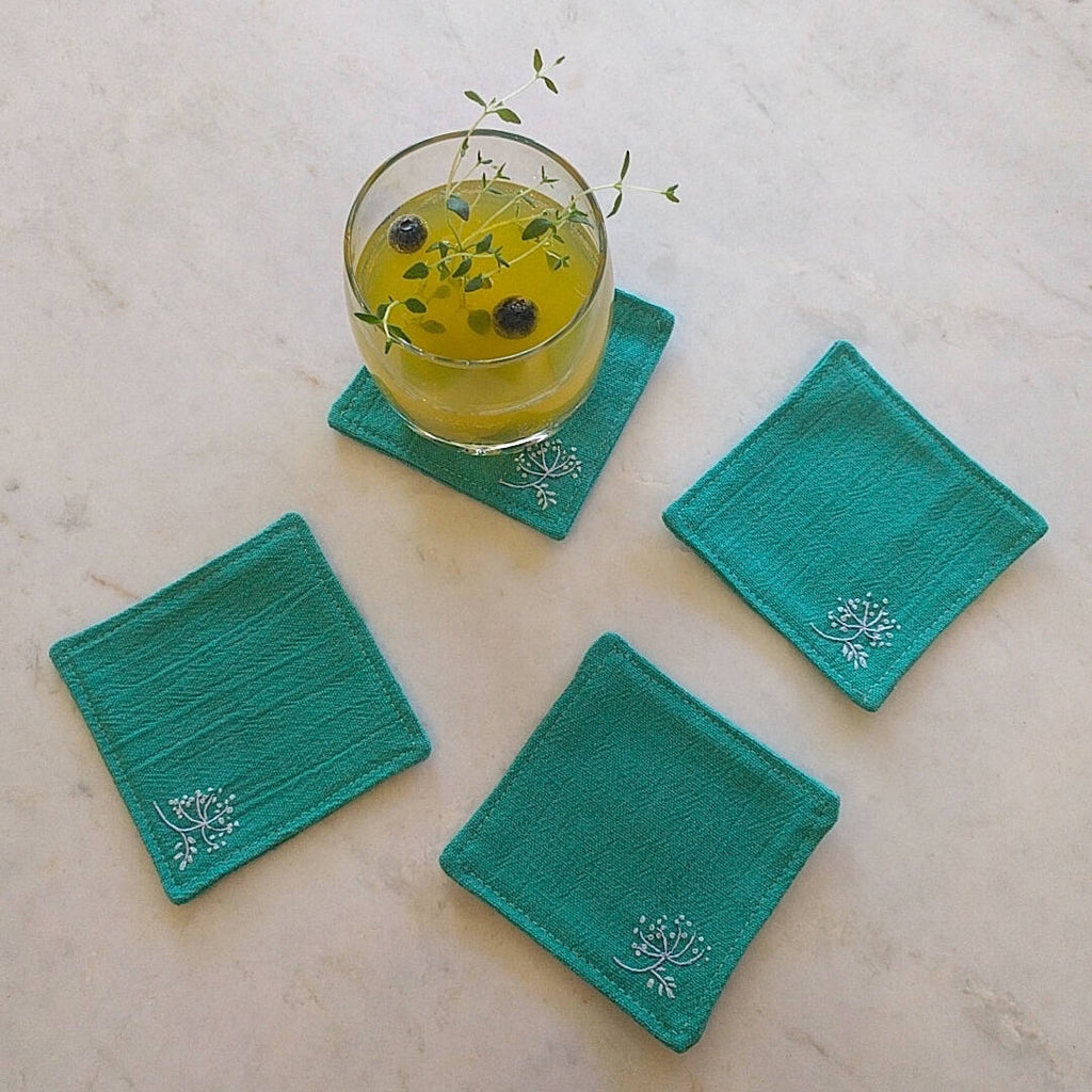 set of four teal green coasters one shown with drink on top