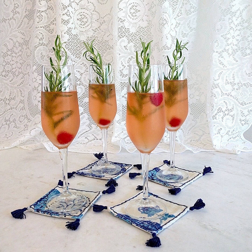 4 square boho in royal blue and ivory heavy linen colored coasters shown under champagne flute drinks