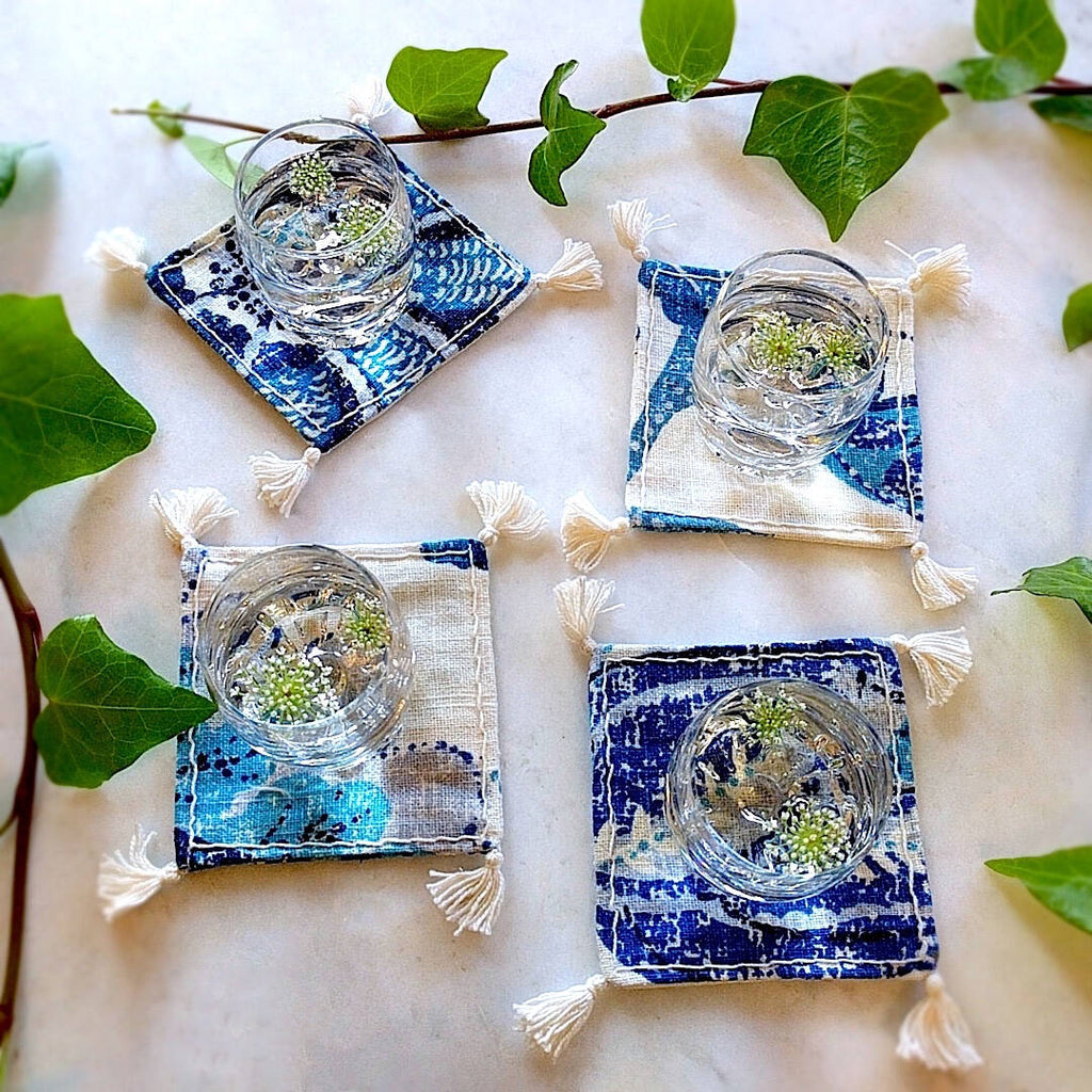 square boho royal blue and ivory colored heavy linen coasters shown under a filled drinks