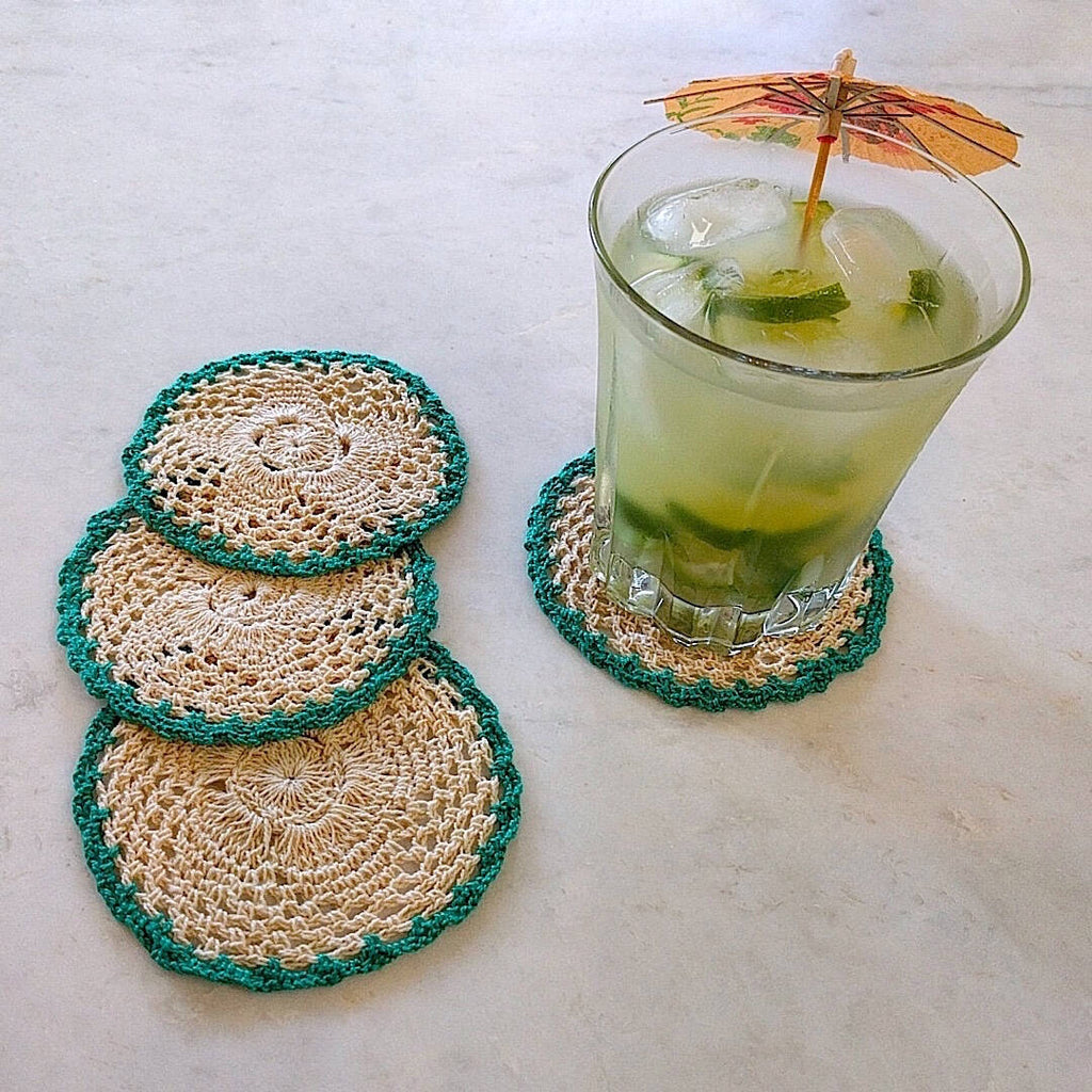 set of four round crochet cotton yarn coasters in natural tan color and teal border - shown with umbrella drink