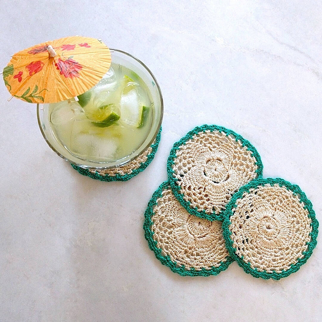 set of four round crochet cotton yarn coasters in natural tan color with teal border - top down view