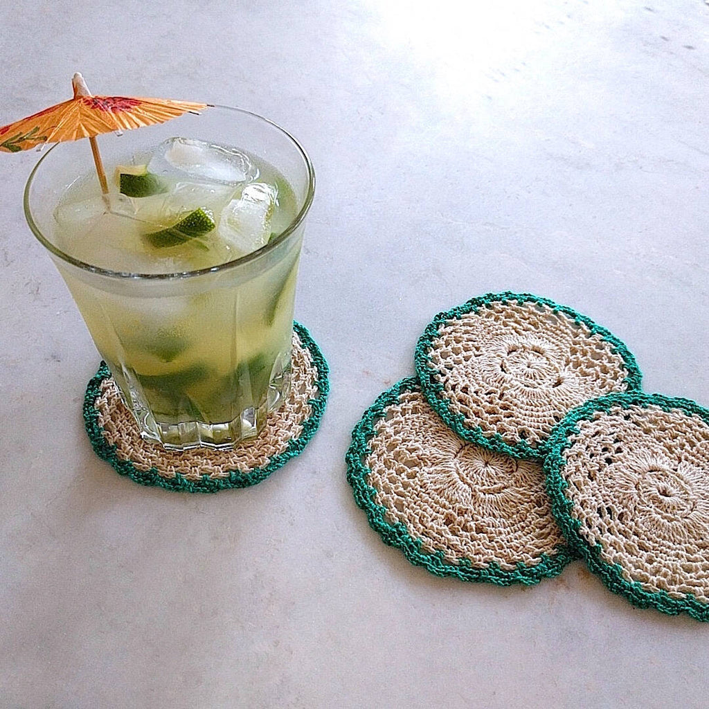set of four round crochet cotton yarn coasters in natural tan color and teal border - one shown with umbrella drink on top