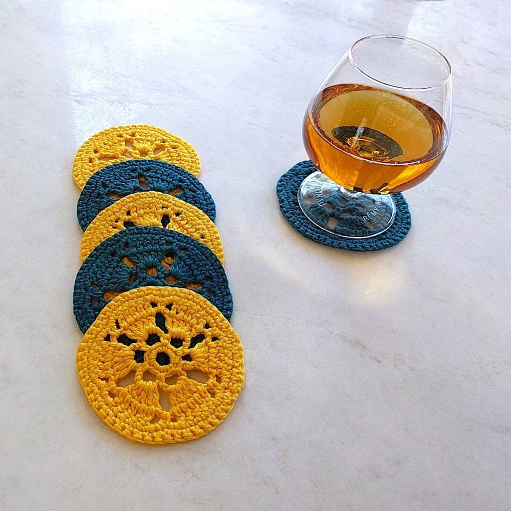 two bright yellow and two earth dark green crocheted coasters shown with a glass of cognac