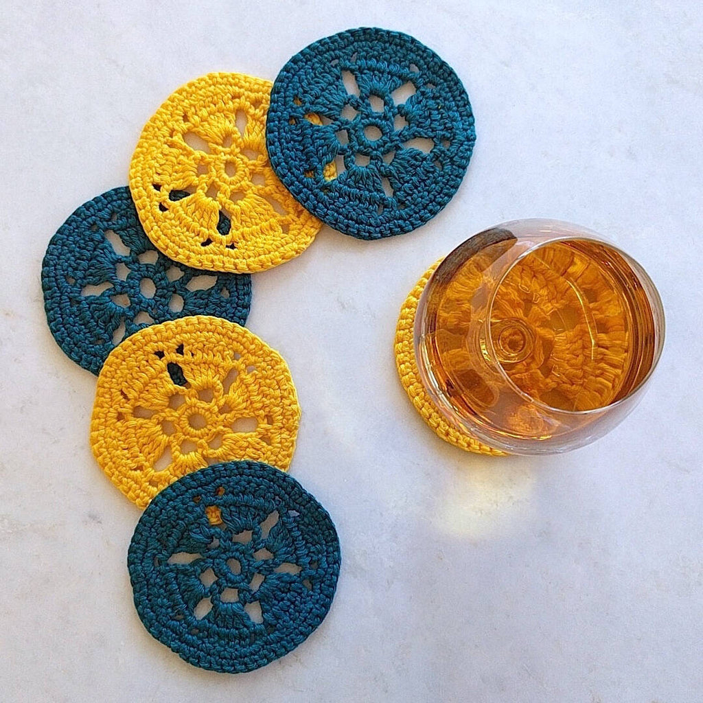 two bright yellow and two earth dark green crocheted coasters - top down view