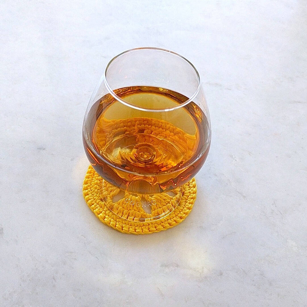 single bright yellow crocheted coaster shown with cognac filled glass