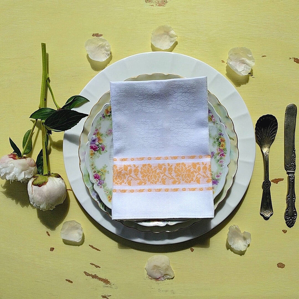 set of four square white cotton napkins with orange detail and flower pattern