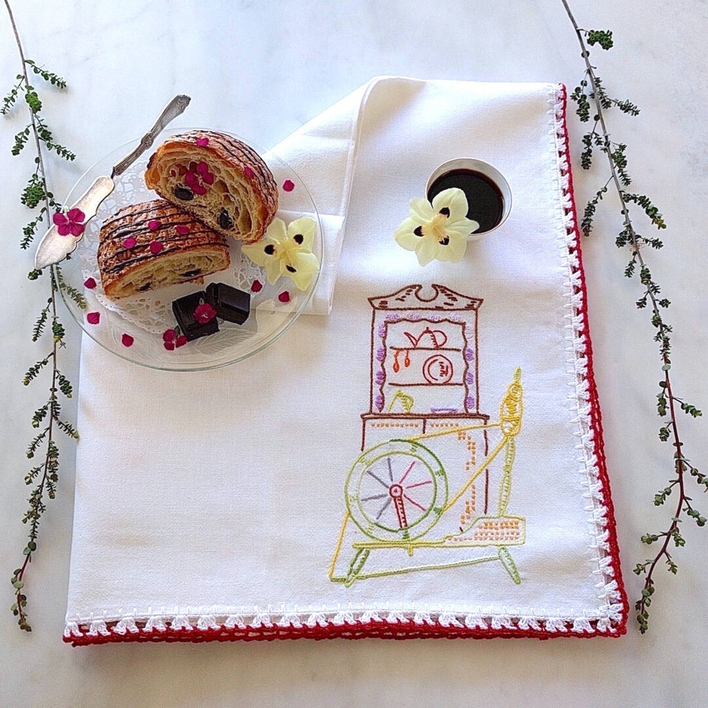 oversized white cotton tea towel with multicolored spinning wheel motif