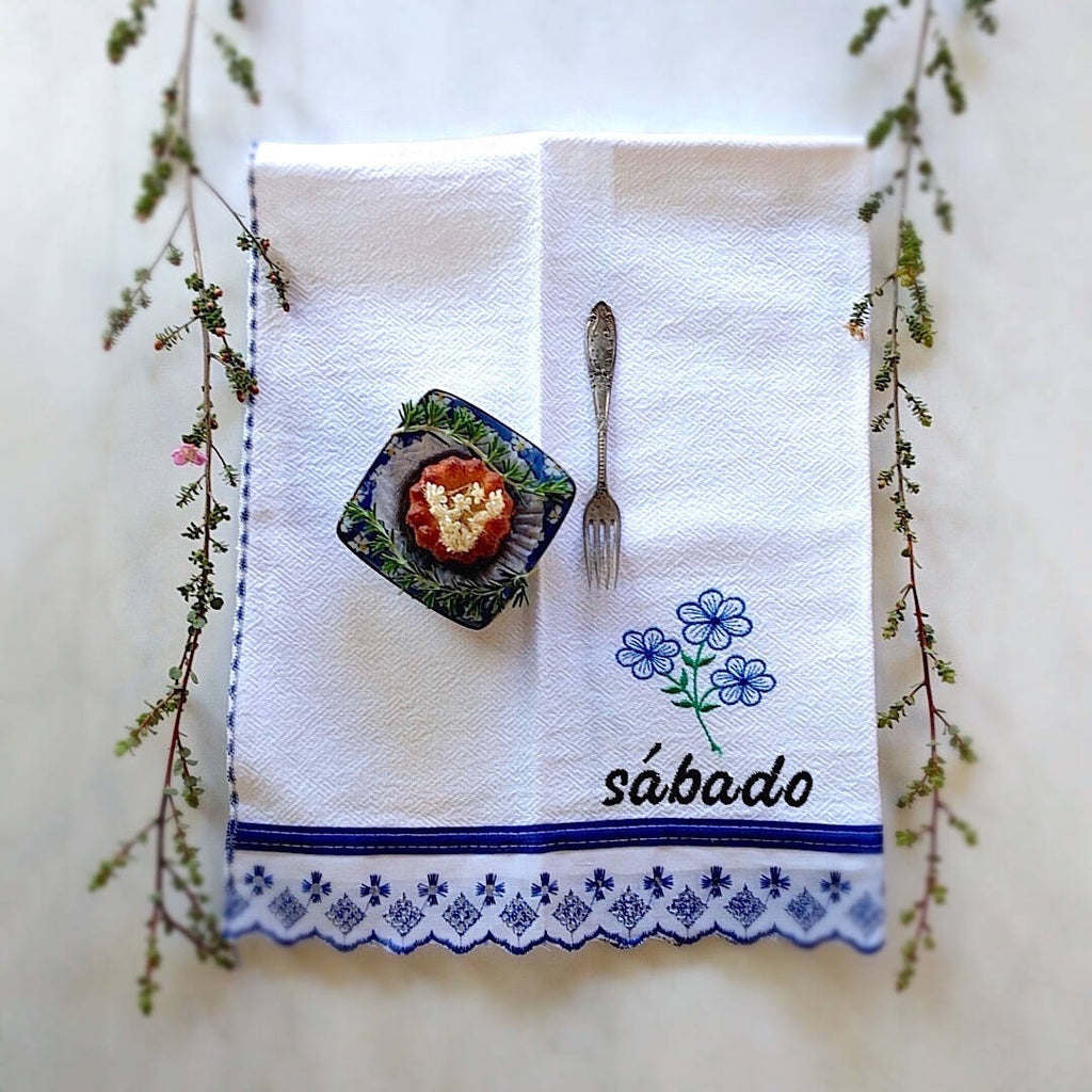 kitchen towel themed with violet trim and day of the week: Sábado