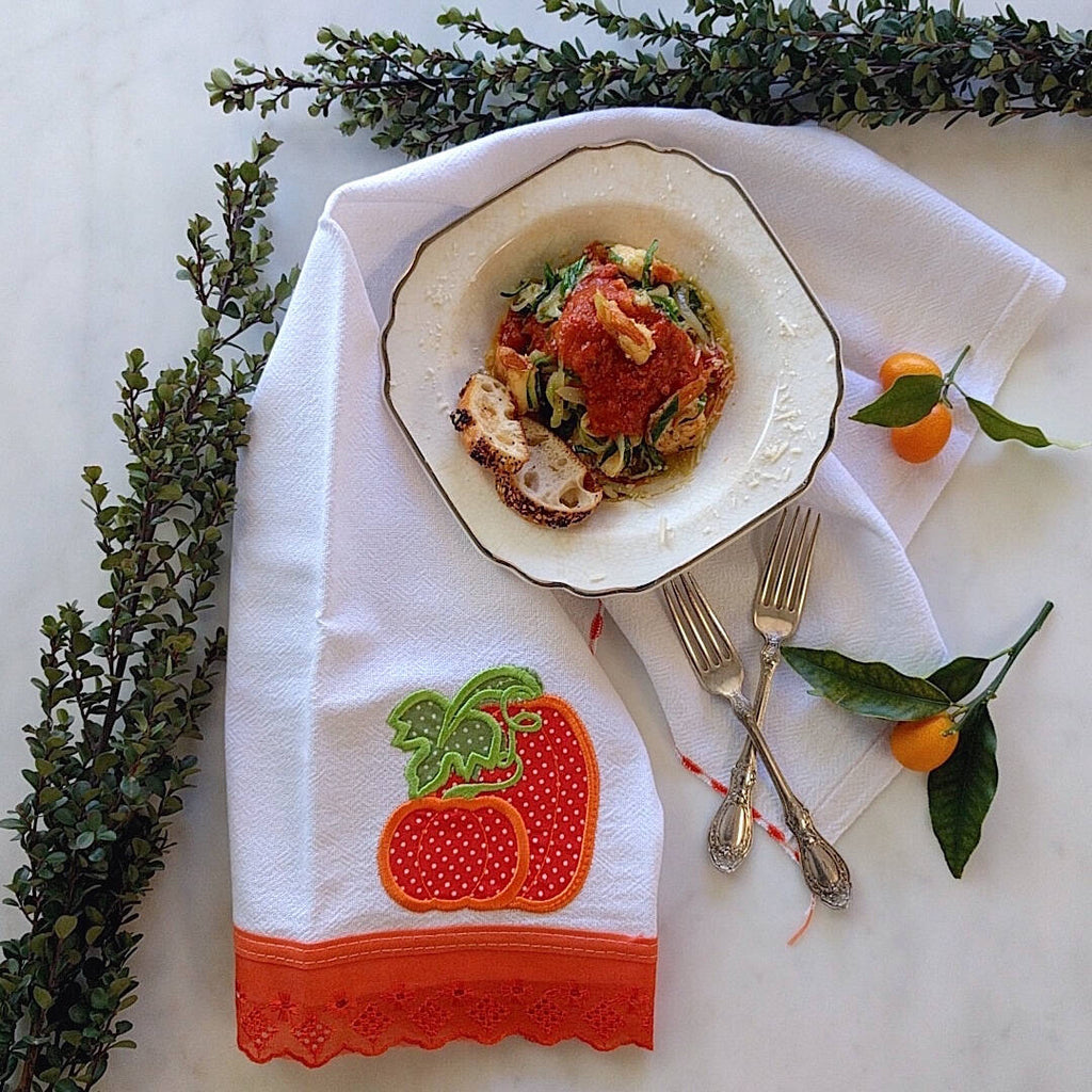 white tea towel with dark orange color strawberry machine embroidered and hemmed