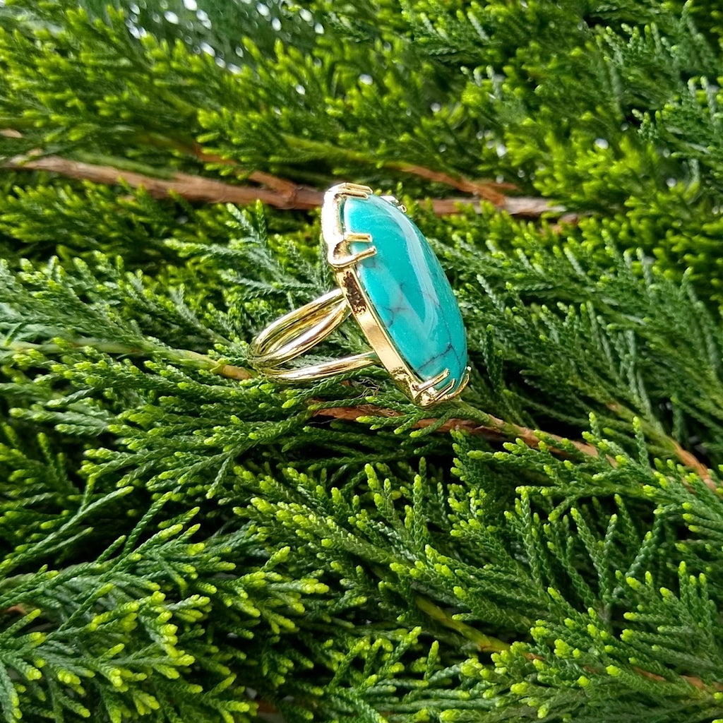 side view of oval turquoise adjustable gold-plated cocktail ring