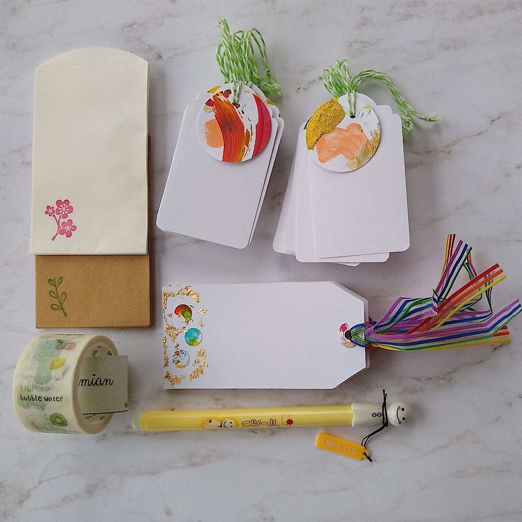 confetti and gold foil gift cards, white gift tags, mini envelopes, Japanese washi tape, Japanese sunny doll black pen laid out differently on a table
