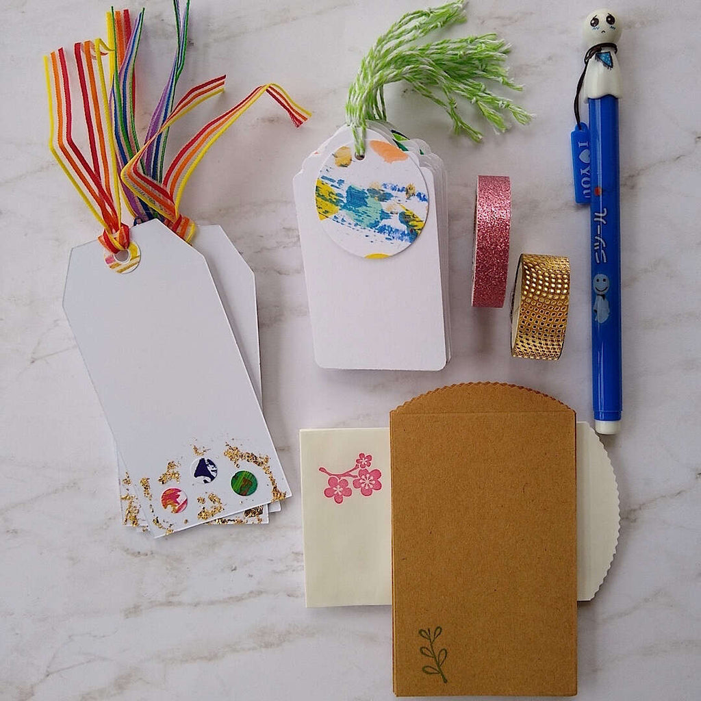 abstract confetti and gold foil gift tags, white gift tags, mini envelopes, Japanese doll pen, Japanese washi tape, laid out a little differently