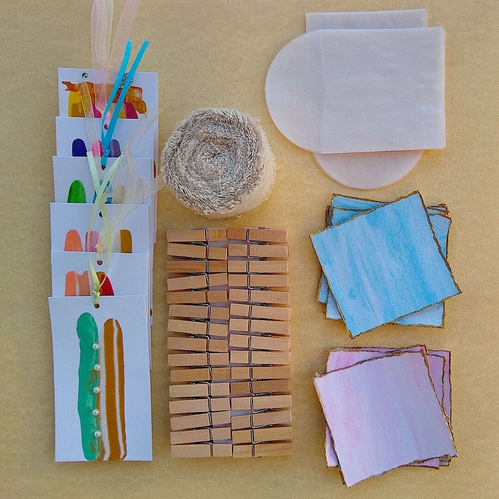 kit contents laid out: abstract gift cards, linen ribbon, wood clothespins, watercolor cards with glassine envelopes