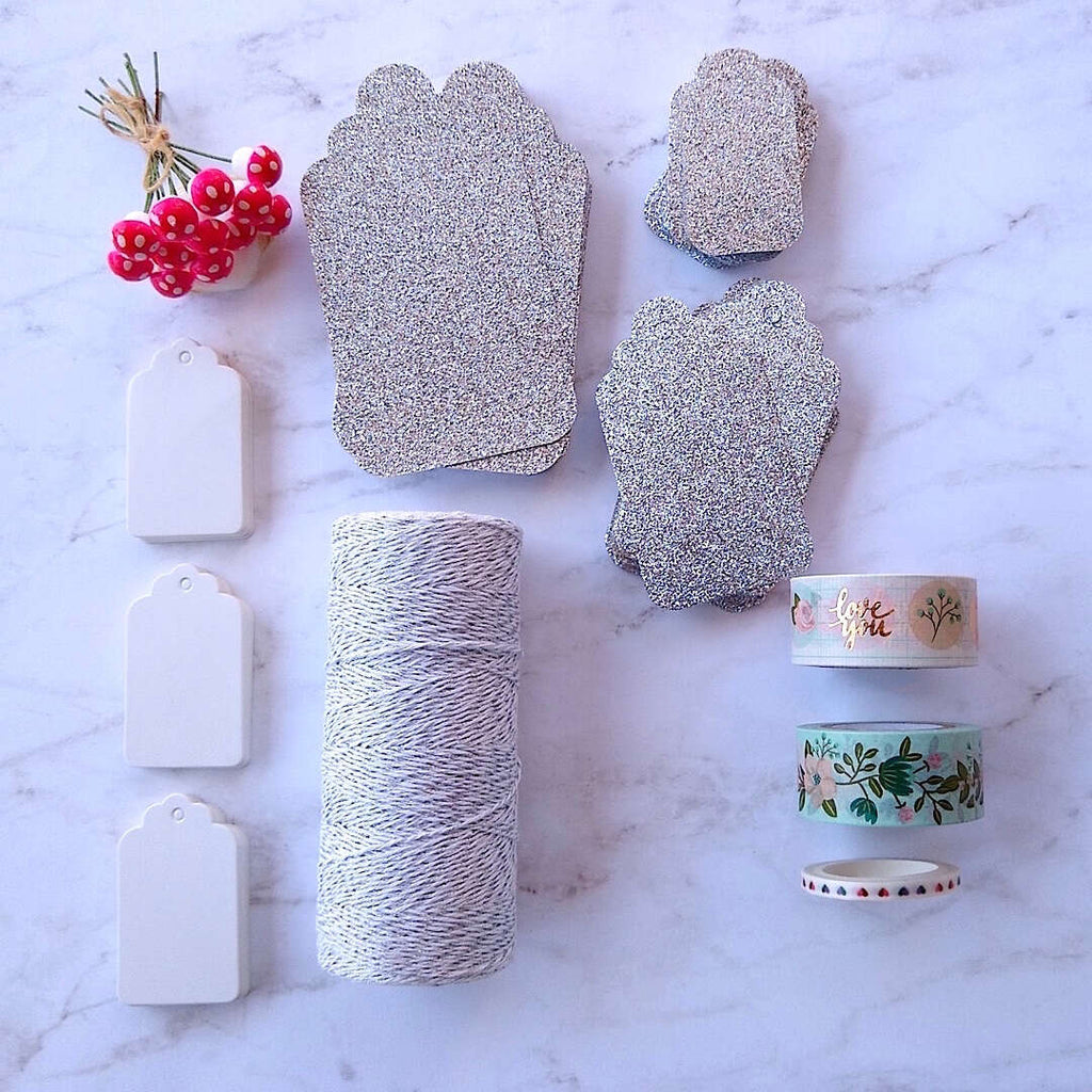silver luxe glitter gift cards, white hang tags, German cotton spun mushrooms, metallic glitter bakers twine differently laid out flat