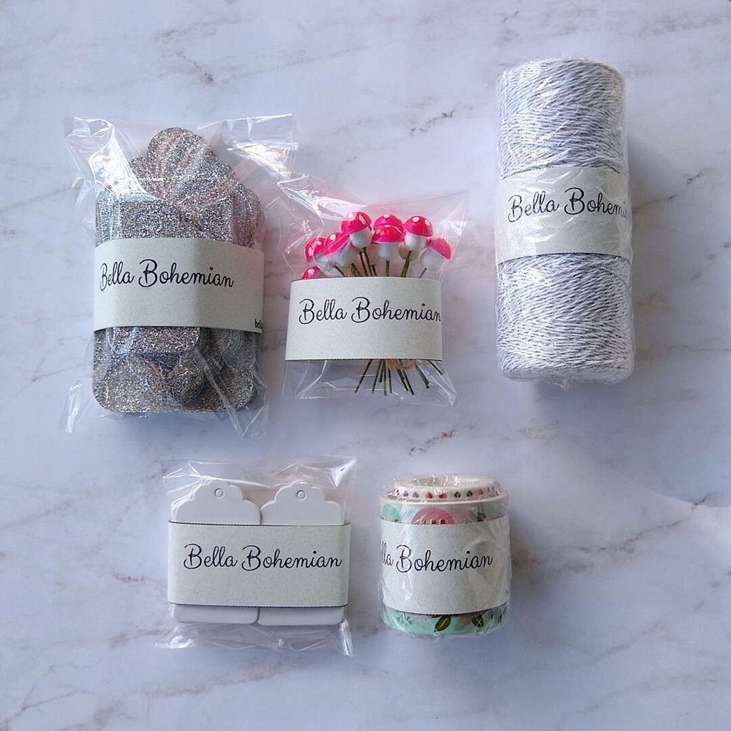 silver luxe glitter gift cards, white hang tags, German cotton spun mushrooms, metallic glitter bakers twine plastic wrapped laid out flat