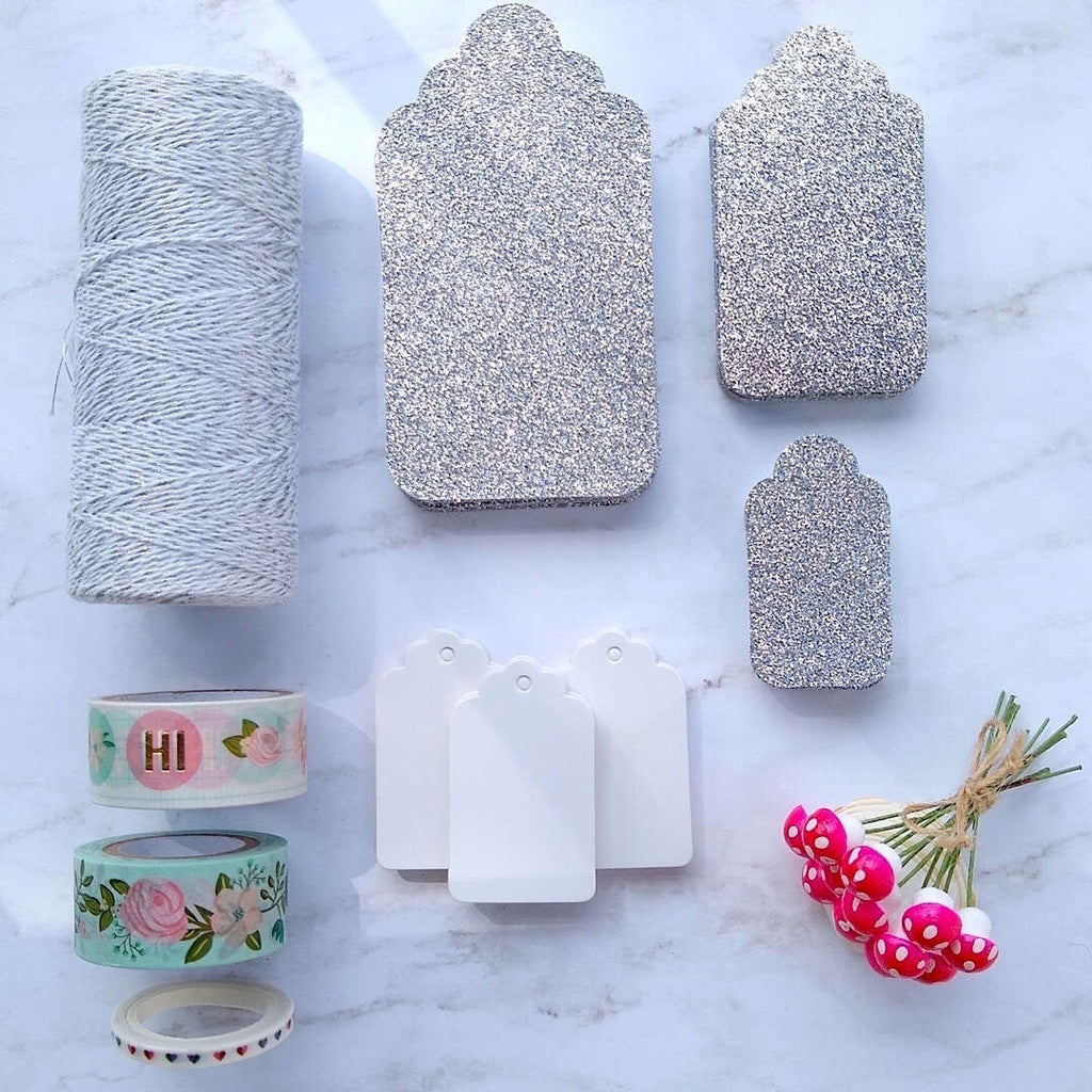 silver luxe glitter gift cards, white hang tags, German cotton spun mushrooms, metallic glitter bakers twine laid out flat