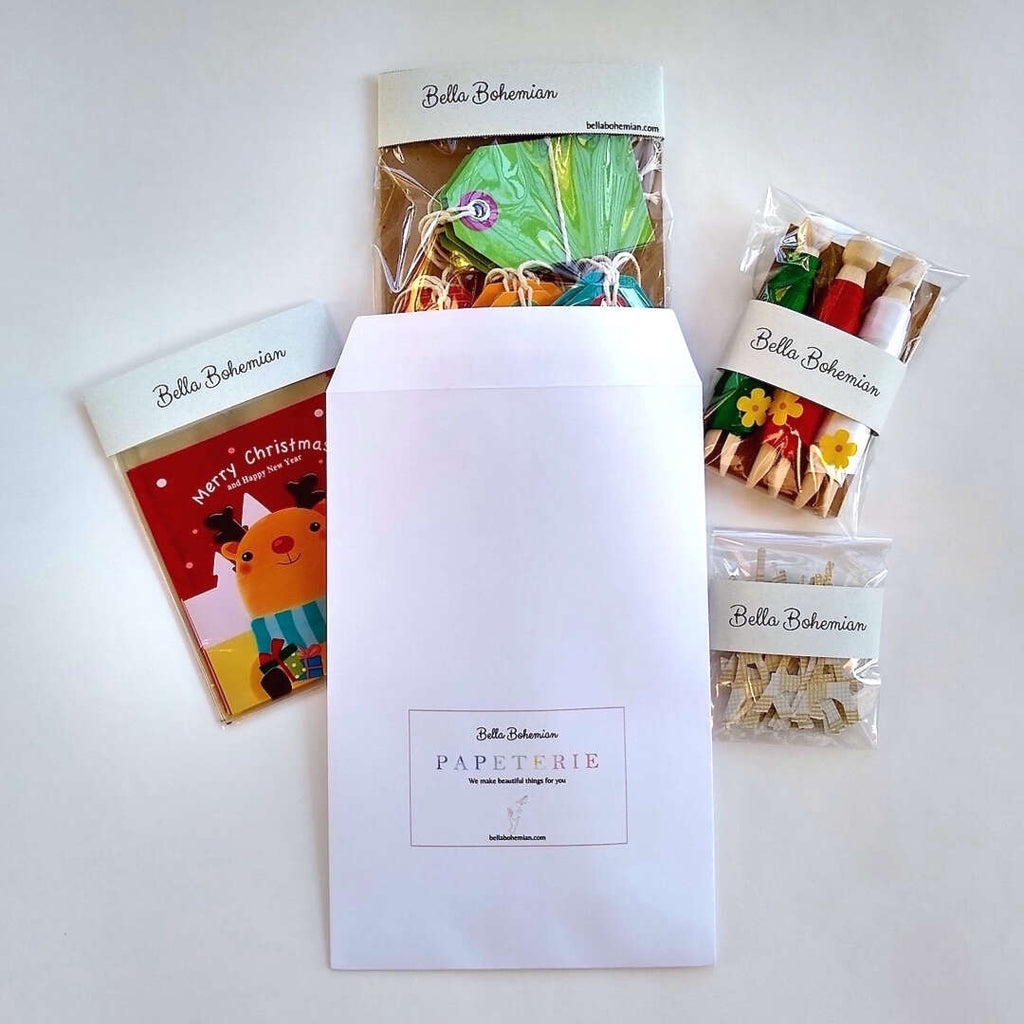 Bella Bohemian envelope with wrapped packages of Christmas favor bags, gift ribbons, gift tags and eiffel tower confetti
