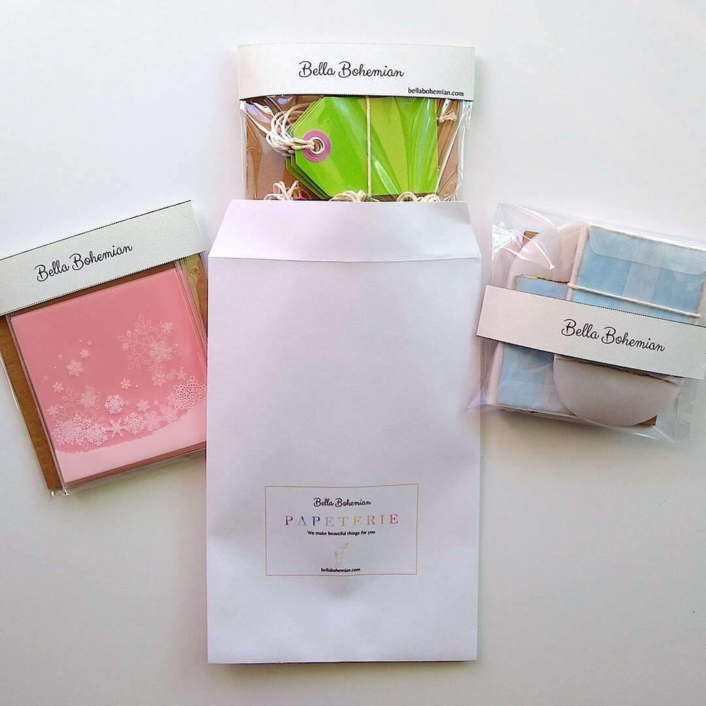 3 wrapped papeterie packs including gift tags, snowflakes favor bags, watercolor cards and glassine envelopes shown with Bella Bohemian branded envelope