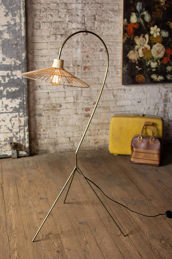 brass finish floor lamp with three legs and rattan shade