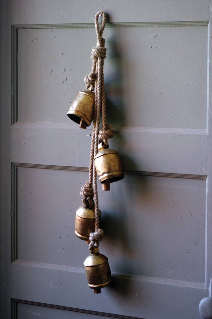 4 rustic iron cow bells hanging on rope