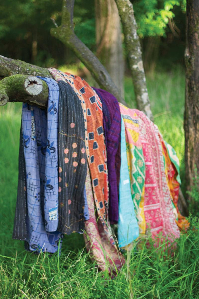 several kantha throws of different colors hung over a tree branch