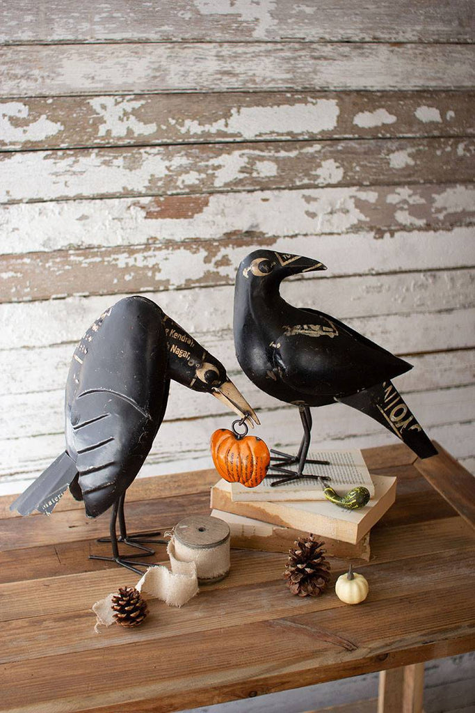two black iron crows one holding a pumpkin