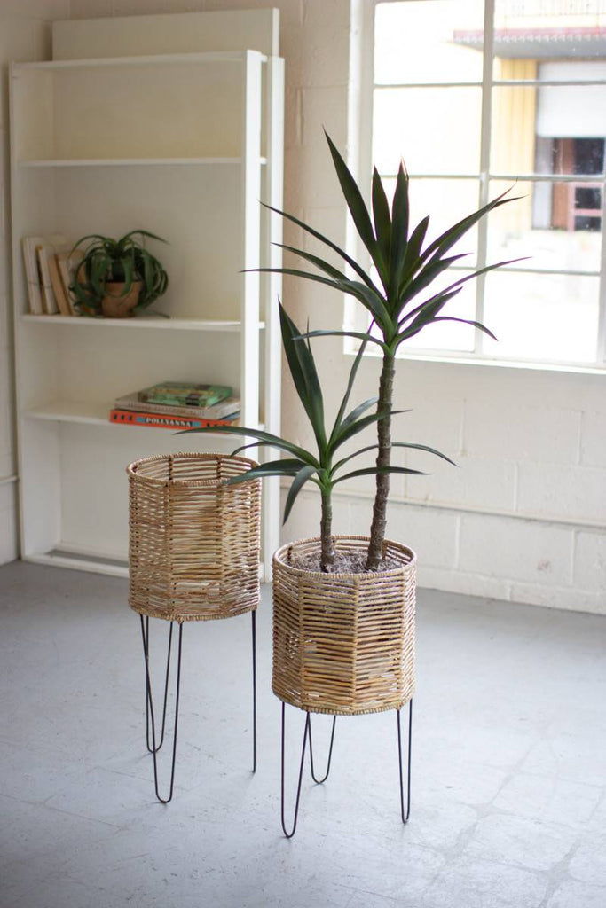 two round seagrass planters with iron legs