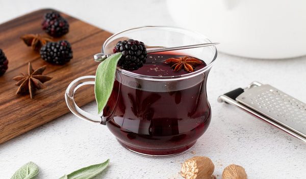 Gluhwein in glass with blackberry sage garnish