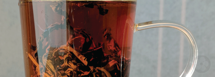 Whole black tea leaves steeping in a glass infuser mug