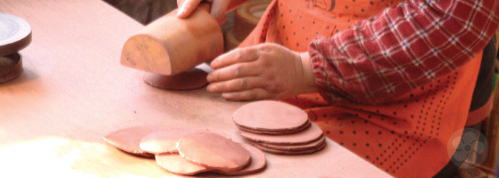 round patties of clay are flattened by hand with a wooden mallet in this yixing workshop