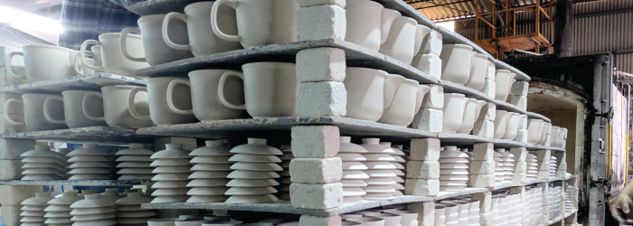 loading a kiln with glazed pottery for a high temperature firing that will vitrify the clay.