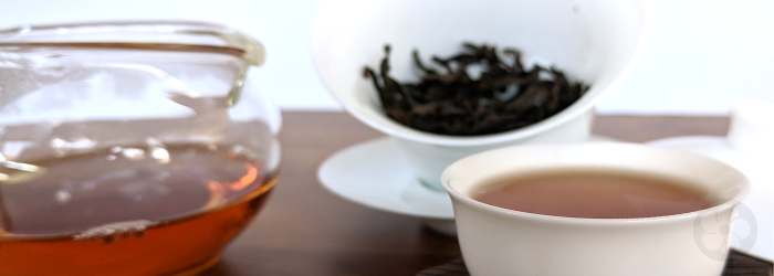 Da Hong Pao leaves in the background produce an amber brew in a glass server and tasting cup