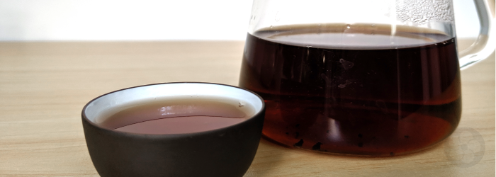 The dark color of aged pu-erh tea shows clearly in a glass server and tasting cup
