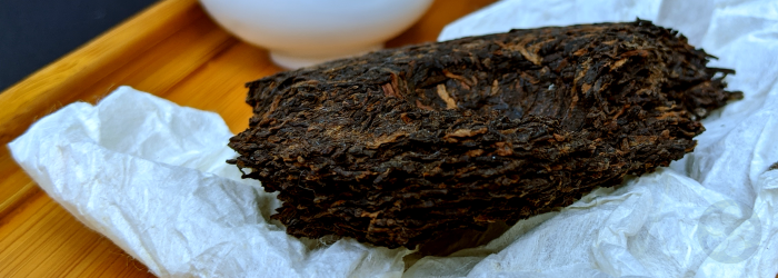 broken pu-erh cake with paper wrapper displays layers of compressed leaves