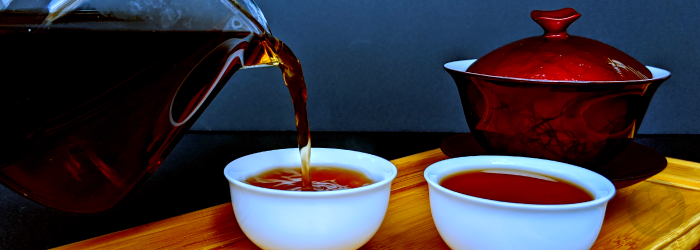 pu-erh tea is served from a glass pitcher into two white tasting cups in front of a red gaiwan