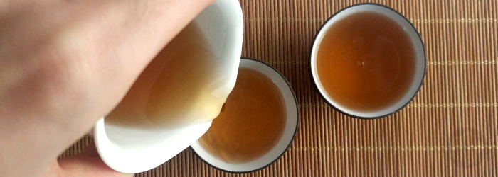 roasted tea is poured from a serving pitcher into two tasting cups on a bamboo mat