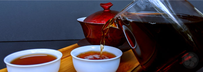 dark pu-erh tea is poured into two small white tasting cups in front of a red gaiwan