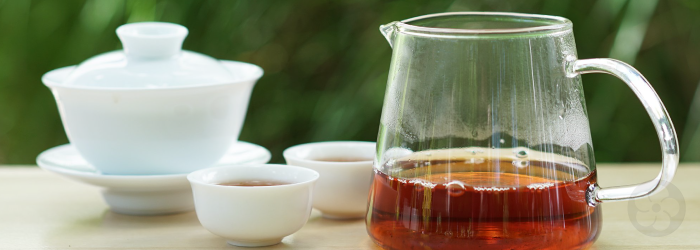 Formosa Red Assam brewed in a porcelain gaiwan and served in a glass pitcher and white tasting cups
