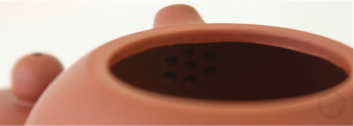 chinese teapots use strainer holes at the base of the spout instead of a basket inserted in the pot.