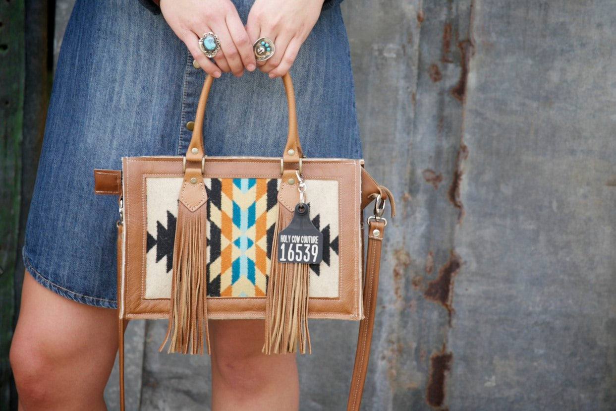 hands holding mini leather tote with black orange and teal mosaic pattern
