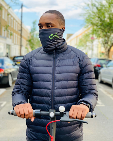 Man on e-scooter wearing pollution mask