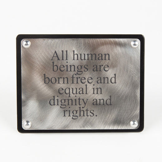 Une plaque en acier inoxydable avec la phrase « All human beings are born free and equal in dignity and rights »