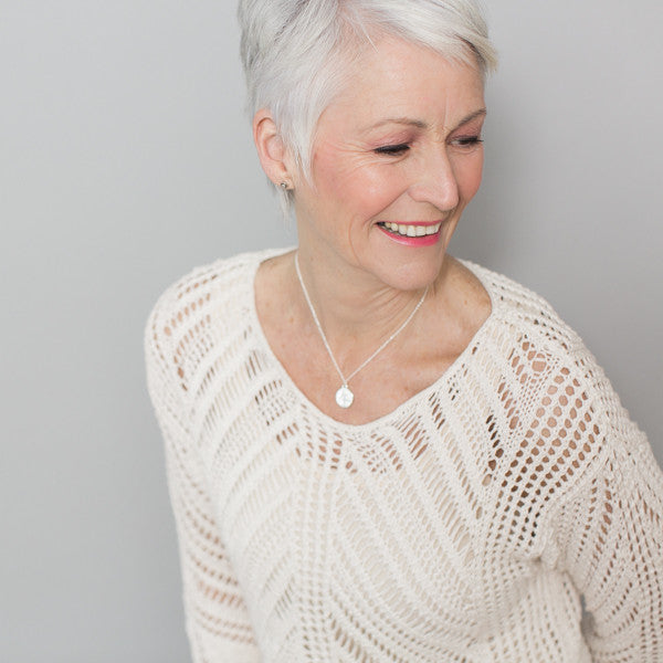 white haired woman wearing necklace supporting charity
