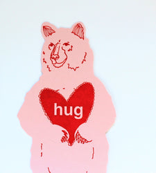 pink bear flat die cut greeting card with red heart that reads hug and holds money