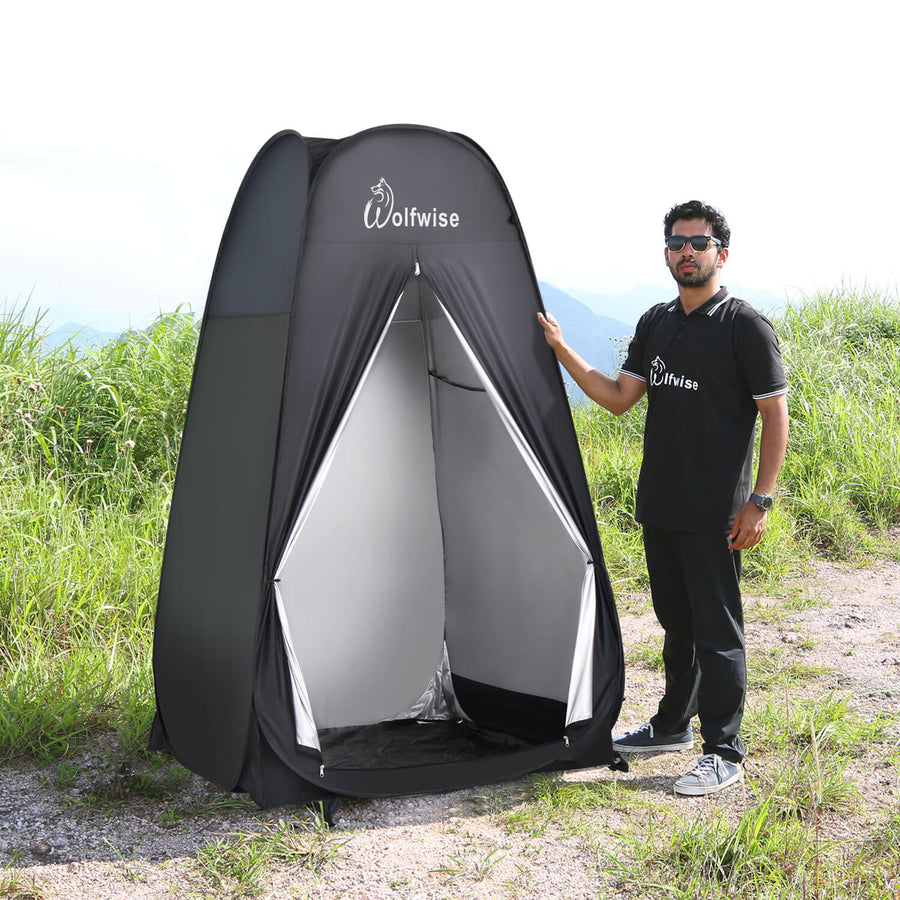 A male model standing next to WolfWise pop up shower tent.