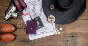 leather travel wallet purple ultraviolet flatlay sun hat vintage camera coins boots passport map mumbai boarding pass wood background explore