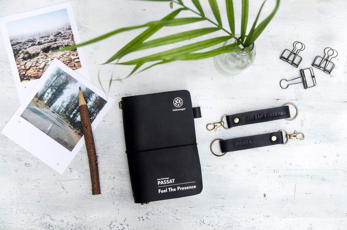 Volkswagen Passat Black Leather Journal and Keychain on table Flatlay